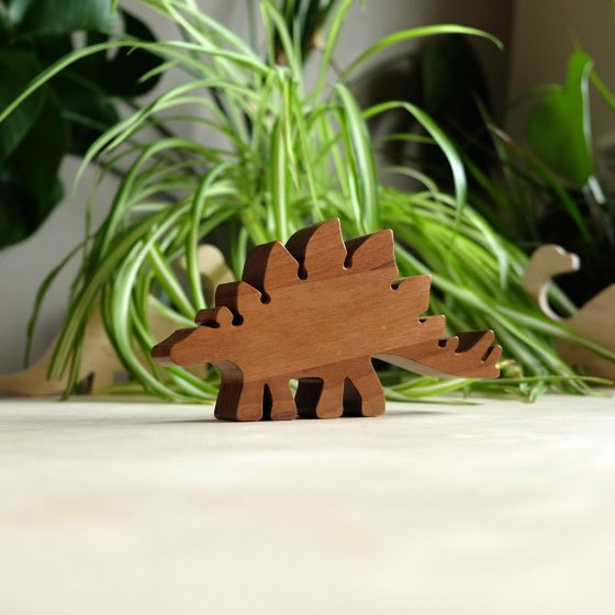 O-WOW sustainably sourced walnut stegosaurus dinosaur toy on a wooden work top in front of a green house plant