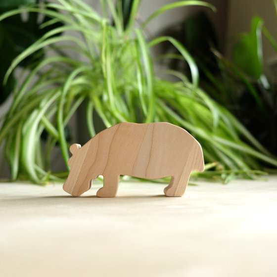 O-WOW eco-friendly maple wood hippo toy on a wooden worktop in front of a green house plant
