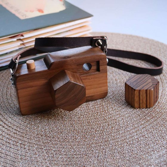 O-WOW handmade wooden camera toy on a woven placemat on a white table next to a close book
