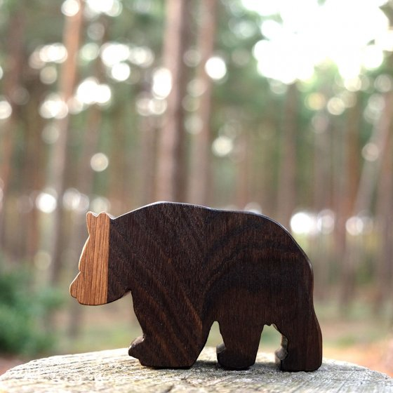 Close up of O-WOW Dark Oak Panda toy stood on a wooden stump in a forrest