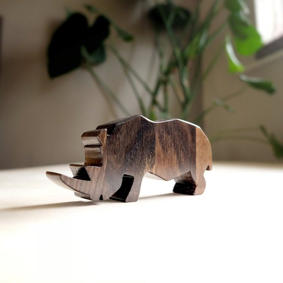 Close up of O-WOW sustainable dark oak Rhino toy on a white floor in front of some green plants