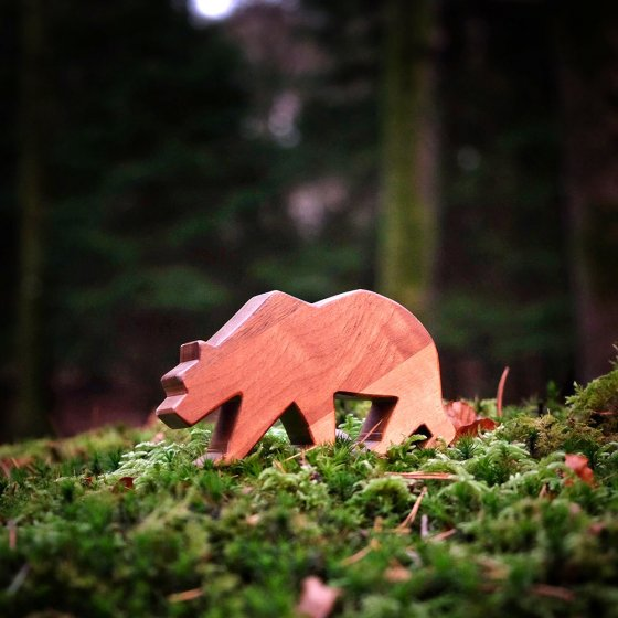 close up of an O-WOW Walnut Bear toy placed on some green moss on a forest floor