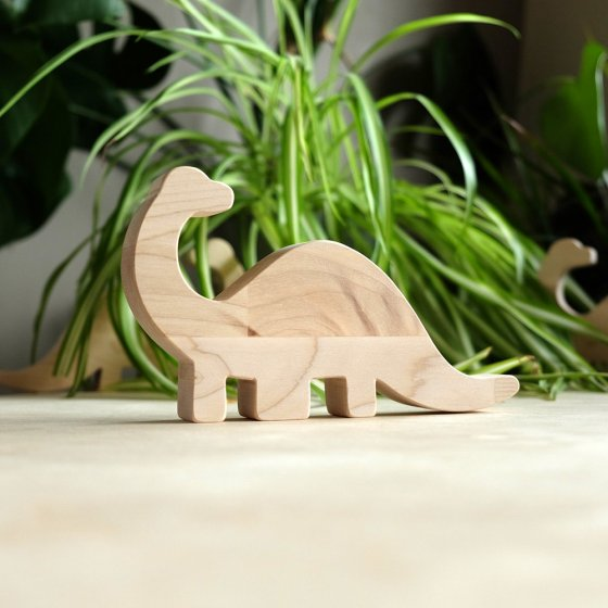 O-WOW sustainable wooden diplodocus toy on a wooden worktop in front of a green house plant