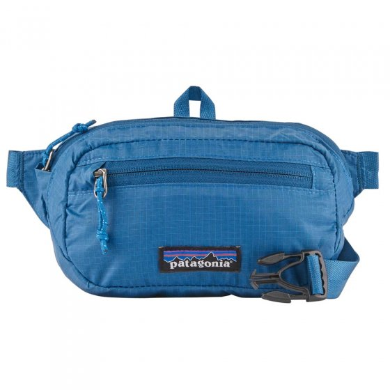 This is a picture of a blue Patagonia hip pack, on top of a white background.