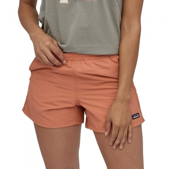 Picture of model wearing the melon colour baggie short. Picture taken front on. Picture background is white.